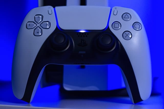 Close-up of white PS5 controller in front of console.